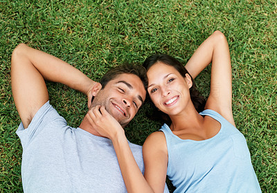 Buy stock photo Affectionate couple smiling while laying in the grass