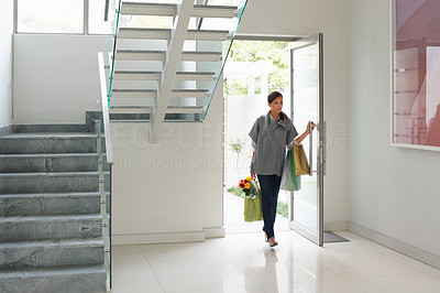 Buy stock photo Stylish young woman entering foyer of modern home with shopping bags - copyspace