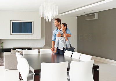 Buy stock photo Happy couple standing in their modern dining room
