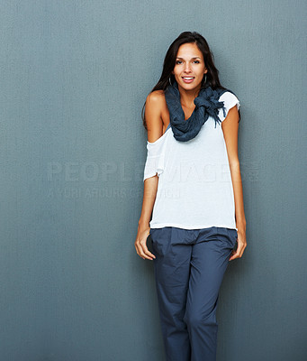 Buy stock photo Woman leaning against blue background with hands in pockets
