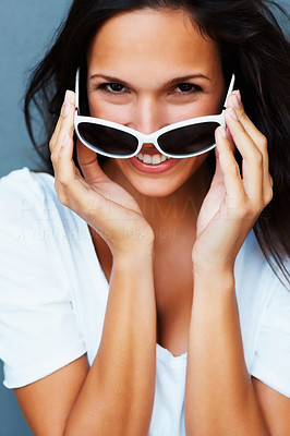 Buy stock photo Pretty woman holding sunglasses on tip of nose against blue background
