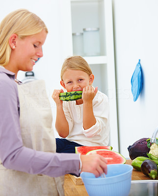 Mother preparing food in kitchen and her daughter eating