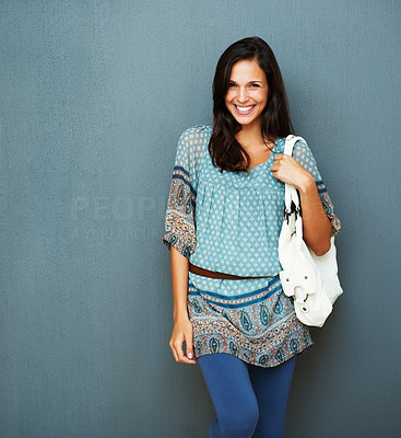 Buy stock photo Woman smiling while holding purse against blue background