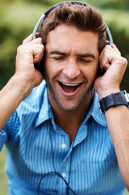 Buy stock photo Shot of a happy young man listening to music ooutdoors