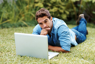 Buy stock photo Portrait of a young man working on laptop in a park