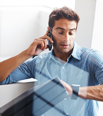 Buy stock photo Shot of a young business man looking at the time while talking on a cellphone