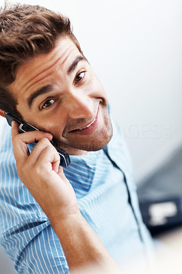 Buy stock photo Portrait of a smiling young man speaking on mobile phone
