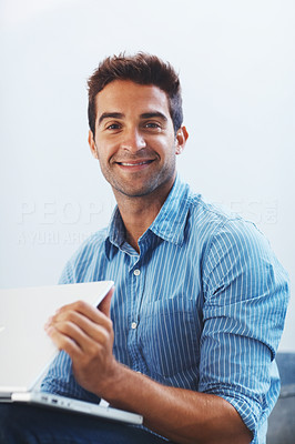 Buy stock photo Portrait of a smiling young man working on laptop