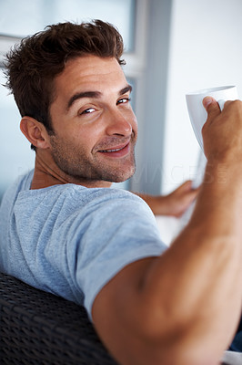 Buy stock photo Portrait of a happy young man glancing backward while having a cup of coffee