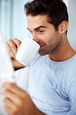 Buy stock photo Shot of a young man drinkng coffee while reading the newspaper