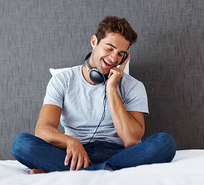 Buy stock photo Shot of a young man sitting on the bed at home and listening to music on headphones