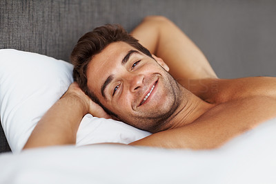 Buy stock photo Portrait of a thoughtful young man relaxing in bed at home