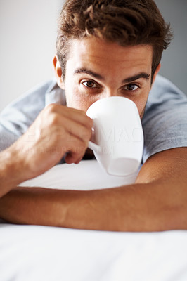 Buy stock photo Portrait of a young man drinking coffee while lying on bed at home - Indoor