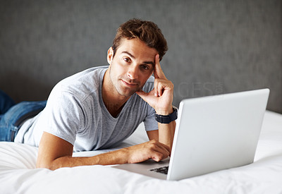 Buy stock photo Portrait of a young man working on laptop while lying on a bed at home