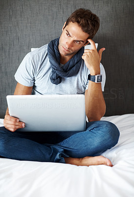Buy stock photo Shot of a thoughtful young man working on laptop while sitting on bed at home