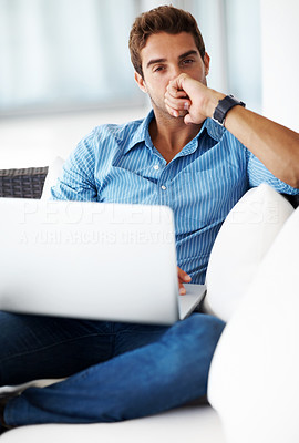 Buy stock photo Shot of a thoughtful young man using laptop while sitting on couch at home