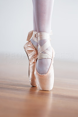 Buy stock photo Low angle shot of a ballet dancer's feet on wooden floor while wearing pointe shoes