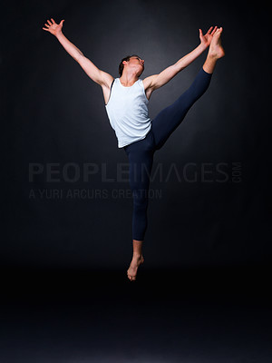 Buy stock photo Full length of a male ballet dancer dancing energetically against black background - copyspace