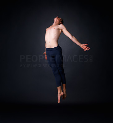 Buy stock photo Full length of a young male ballet dancer flying against black background