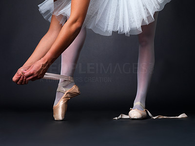 Buy stock photo Low angle view of a ballerina putting on pointes against black background