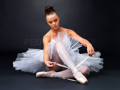 Buy stock photo Full length of a young ballerina puts on Pointe against black background