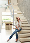 Relaxed mid adult woman sitting on stairs in a modern house