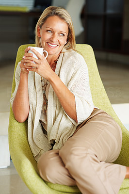 Buy stock photo Portrait of a beautiful middle aged woman with a cup of tea or coffee smiling over a thought