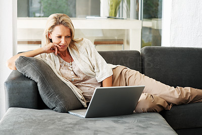 Buy stock photo A pretty and relaxed middle-aged woman using a laptop on the couch