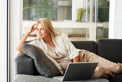 Buy stock photo Portrait of a thoughtful middle aged woman lying on sofa while using laptop