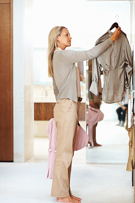 Buy stock photo Side view of a mature woman choosing outfit at home