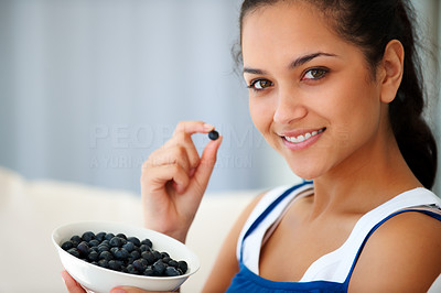 Buy stock photo Portrait of pretty happy young girl eating blackberries at home - Indoors