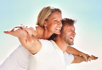 Buy stock photo Happy couple enjoying themselves out in the open, female on man's back pretending to fly with bright sky background