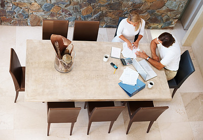 Buy stock photo Mature couple at home with modern dining room working on laptop on house finance