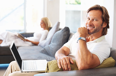 Buy stock photo Portrait of a happy casual man using laptop with woman reading book in the background at home