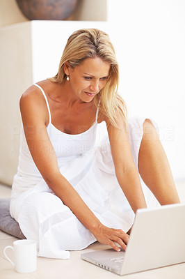 Buy stock photo Portrait of a middle aged woman sitting on floor using laptop