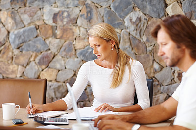 Buy stock photo A mature couple at dining table working on laptop on house finance