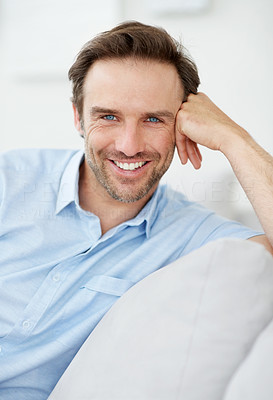Buy stock photo Portrait of a satisfied young man smiling while sitting on couch - Indoor