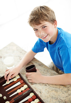 Buy stock photo Portrait of a smiling little boy playing backgammon game - Indoor