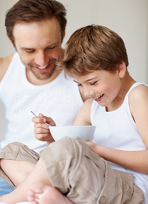 Buy stock photo Portrait of a smiling young father and son eating breakfast together