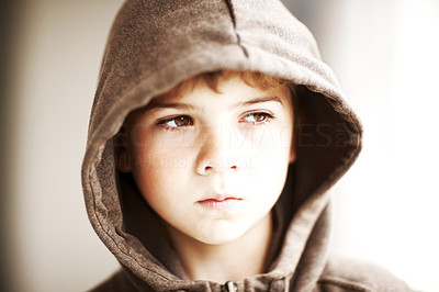 Buy stock photo Portrait of a small boy in a hoodie looking sad and serious