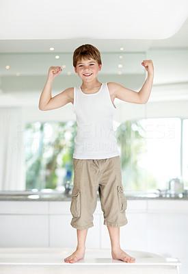 Buy stock photo Portrait of a funny little boy standing on kiitchen and showing his muscles