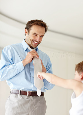 Buy stock photo Portrait of a happy young man getting ready for office and a small boy pointing at his necktie