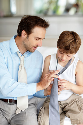 Buy stock photo Portrait of a caring young father showing his son how to wear tie at home