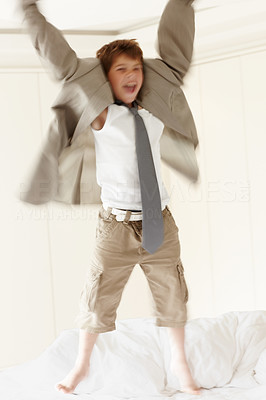 Buy stock photo Portrait of an excited little kid wearing an oversized coat jumping on bed
