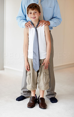 Buy stock photo Portrait of a little young boy wearing his father's shoes and standing with his father