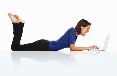 Buy stock photo Side view of a college student lying on floor and using a laptop against white