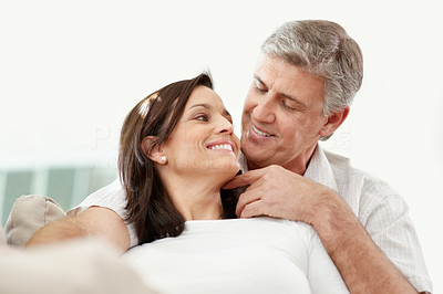 Buy stock photo Portrait of a happy mature couple relaxing at home and smiling
