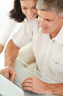 Buy stock photo Portrait of a mature man showing something interesting to his wife on laptop