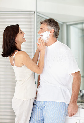 Buy stock photo Portrait of a beautiful lady shaving her husband in washroom