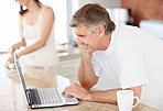 Mature man using a laptop with his wife working in kitchen